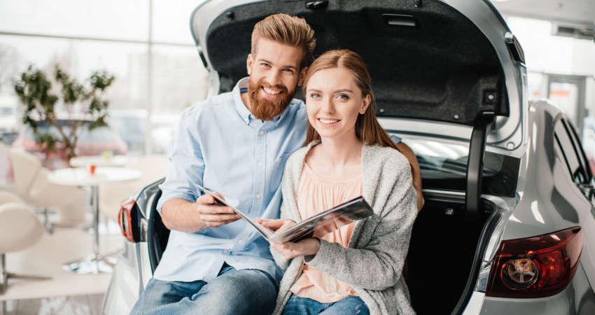 para siedząca w bagażniku samochodu przeglądająca katalog