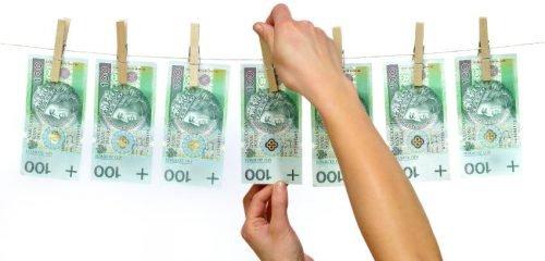 kobiece dłonie wieszające na sznurku banknoty stuzłotowe
