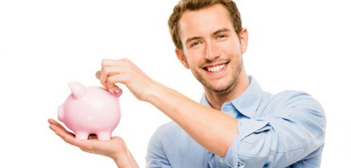 mężczyzna trzymający w ręce świnkę skarbonkę