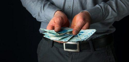 mężczyzna trzymający w dłoniach banknoty