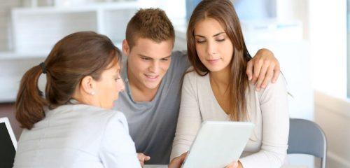doradca pokazuje coś mężczyźnie i kobiecie na ekranie tabletu