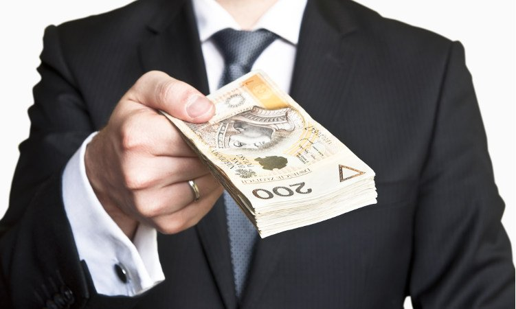 mężczyzna w garniturze przekazujący plik banknotów