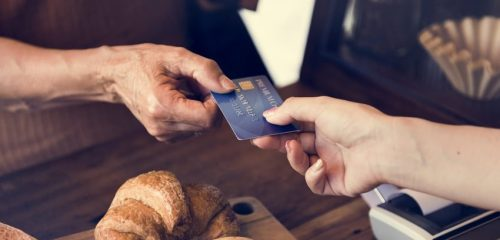 kobieta dokonująca zakupu zakupu w piekarni za pomocą karty prepaid