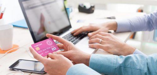 różowa karta kredytowa w dłoniach w tle osoba dokonująca zakupu przez laptopa