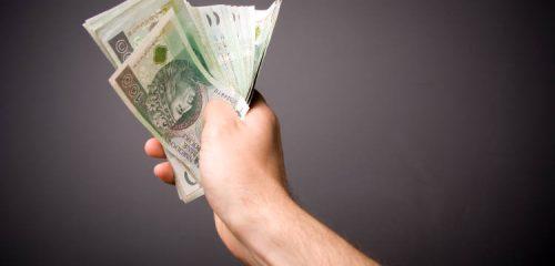 banknoty stuzłotowe w dłoni mężczyzny