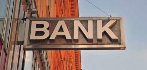 szyld banku na tle fasady i nieba