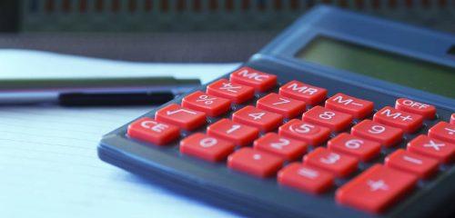 szary kalkulator z czerwonymi przyciskami położony na dokumentach