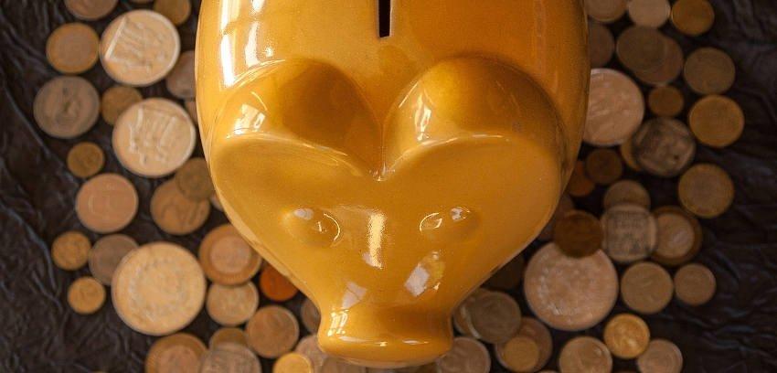 żółta świnka skarbonka na tle rozsypanych monet