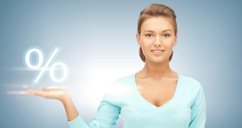 kobieta w niebieskim sweterku podtrzymuje na dłoni biały symbol procenta