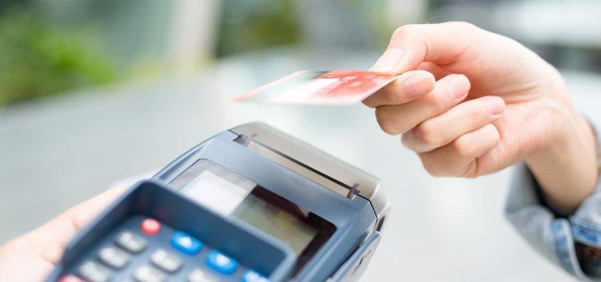 Kobieca dłoń przykładająca kartę płatniczą do terminala pos