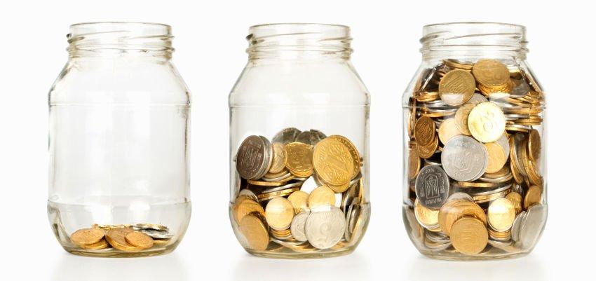 trzy słoiki w wypełnione monetami nawiązujące do pomniejszania zysków o podatek Belki