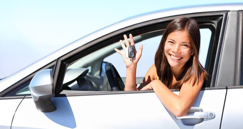 kobieta wyglądająca przez okno samochodu pokazuje zawieszone na palcu kluczyki
