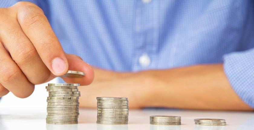 Mężczyzna w błękitnej koszuli ustawia słupki monet - od najniższego do najwyższego