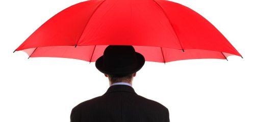 mężczyzna w czarnym meloniku i garniturze stoi pod czerwonym parasolem