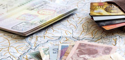 położony na mapie paszport, banknoty i portfel z kartami płatniczymi
