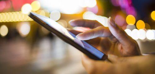 smartfon w kobiecych dłoniach na tle świateł miasta