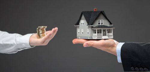 monety na dłoni jednej osoby oraz model domu jednorodzinnego na dłoni drugiej osoby
