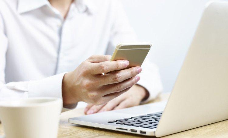 kobieta w białej koszuli siedząca przed laptopem z telefonem w dłoni