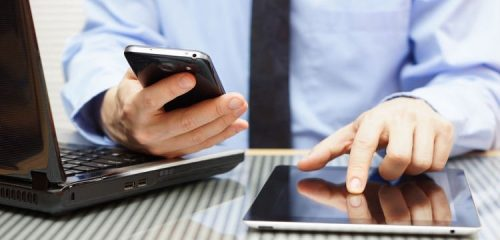 mężczyzna w niebieskiej koszuli pracujący na laptopie, smartfonie i tablecie