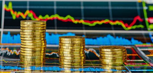 trzy słupki złotych monet na tle wykresów giełdowych