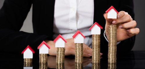 kobieta w białej koszuli układająca na słupkach z monet miniaturowe domki