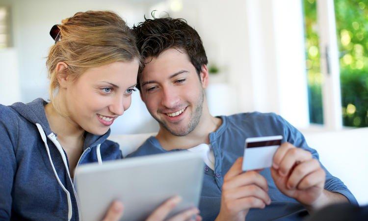 mężczyzna trzymający w dłoniach kartę płatniczą i kobieta trzymająca tablet