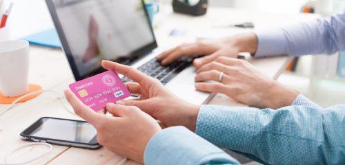 różowa karta kredytowa w dłoniach w tle laptop