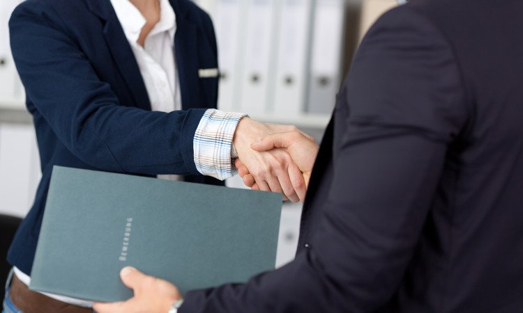 kobieta ściskająca męską dłoń podczas procesu rekrutacyjnego