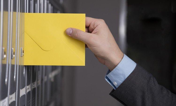 męska dłoń wsuwająca żółtą kopertę do skrzynki na listy