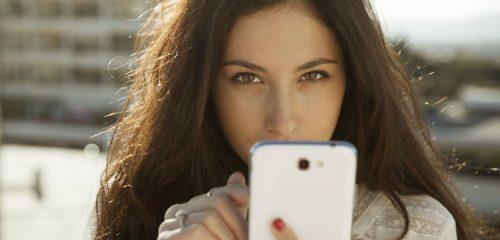 kobieta spoglądająca zza białego smartfona
