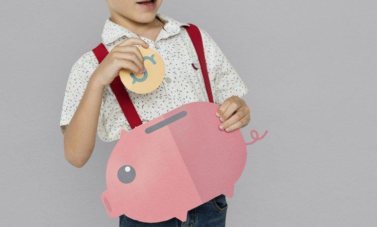 dziecko trzymające wyciętą z papieru świnkę skarbonkę i wyciętą monetę