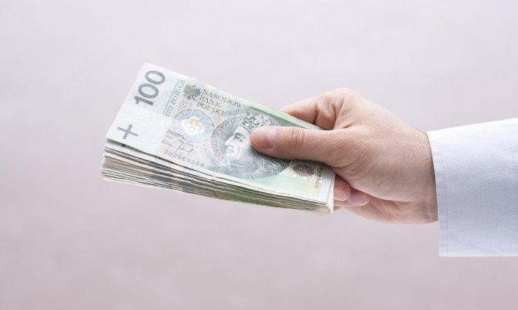 dłoń przekazująca plik stuzłotowych banknotów