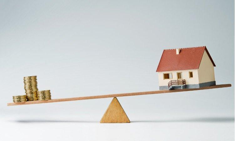 model domku i złote monety na równoważni