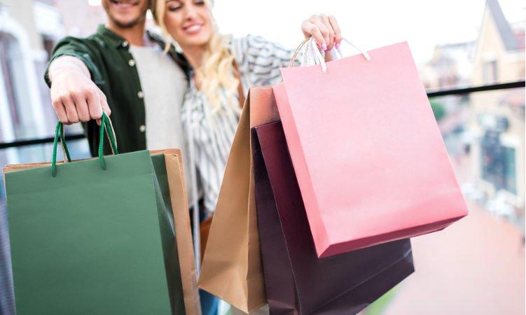 mężczyzna z kobietą trzymający w dłoniach kolorowe torby z zakupami