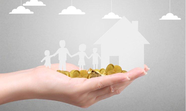 wycięta z papieru rodzina i dom na dłoni ze złotymi monetami
