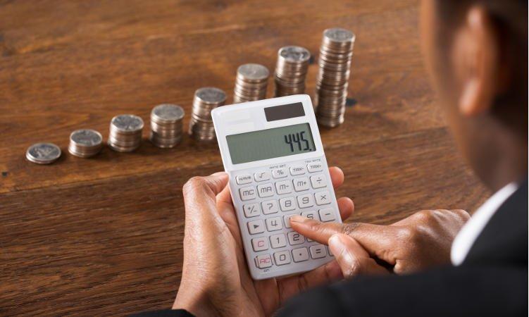 mężczyzna używający kalkulatora w tle słupki monet