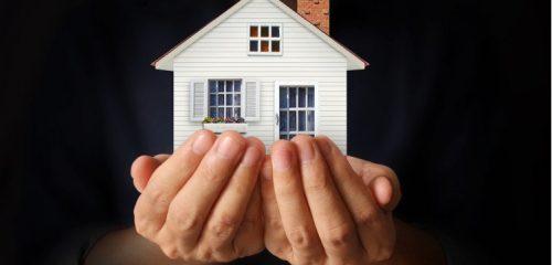 model białego domu w dłoniach na czarnym tle