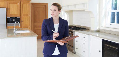 kobieta z teczką i długopisem dokonuje oględzin nieruchomości