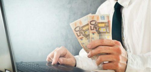 mężczyzna siedzący przy laptopie trzymający w dłoni dwa banknoty