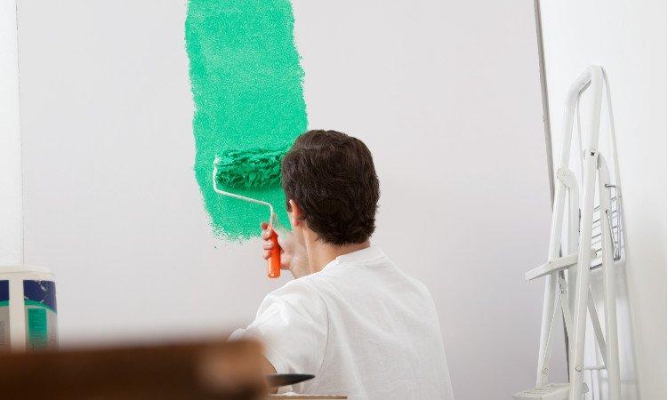 mężczyzna malujący wałkiem ścianę na zielony kolor