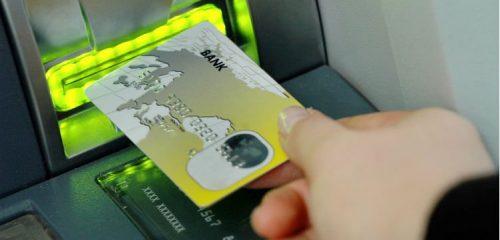 mężczyzna wsuwający kartę do szczeliny bankomatu