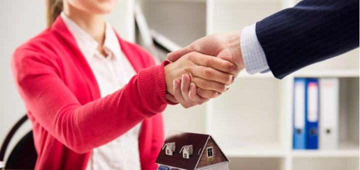 biznesowy uścisk dłoni nad makietą domu