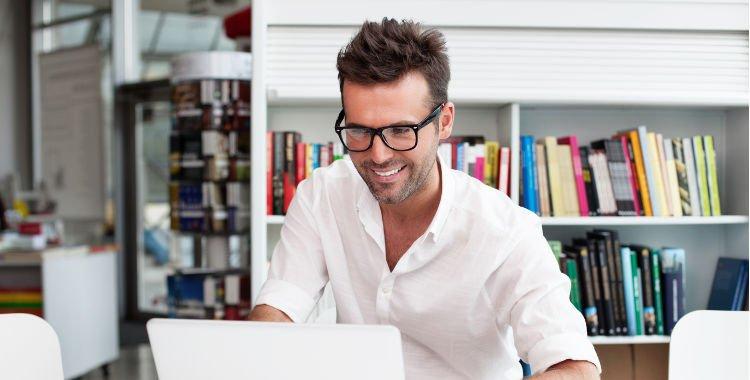 mężczyzna w białej koszuli przed laptopem