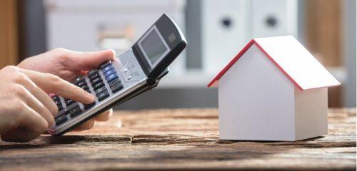 makieta domu i dłoń z kalkulatorem