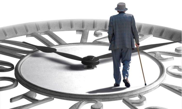 mężczyzna z laską idący po dużej tablicy zegara
