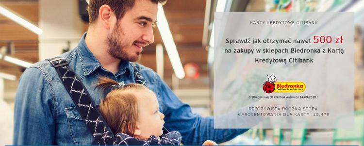 mężczyzna z dzieckiem w nosidełku robiący zakupy