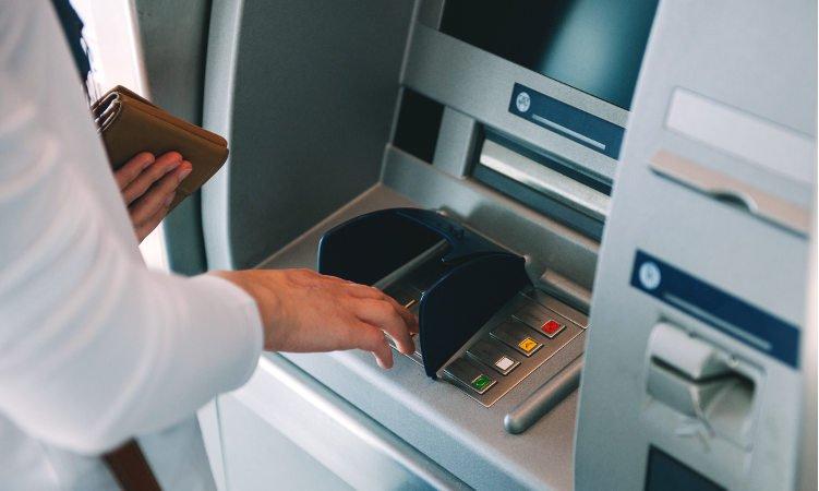 osoba w białej koszuli wypłacająca gotówkę z bankomatu