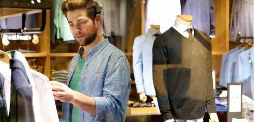 młody mężczyzna oglądający koszulę w sklepie