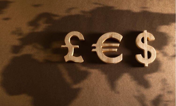symbole walut euro, funta i dolara na tle mapy