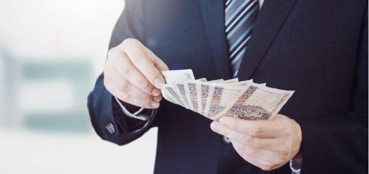 mężczyzna w garniturze z wachlarzem banknotów